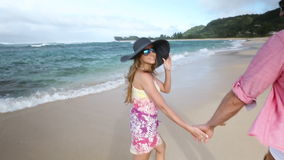 Loving young Caucasian couple holding hands walking together beach Oahu Hawaii. Romantic couple in love holding hands on walk on beautiful summer on hawaiian stock footage
