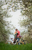 Loving young couple with bicycles in spring garden stock photo