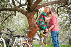 Loving young couple with bicycles in spring garden Royalty Free Stock Photos