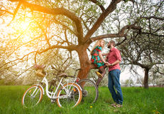 Loving young couple with bicycles in spring garden Royalty Free Stock Photography