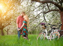 Loving young couple with bicycles in spring garden Stock Image