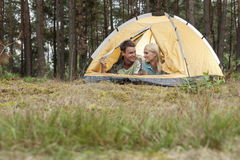 Loving young couple camping in forest Stock Image