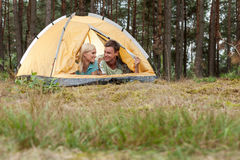 Loving young couple camping in forest royalty free stock photography