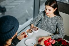Loving young couple celebrating Valentines day holding hands dri. Nking coffee having date at cafe. Relationships, togetherness, love, romantic concept Stock Photo