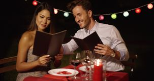 Loving young couple choosing food off a menu. As they enjoy a romantic dinner at a restaurant to celebrate Valentines Day stock video footage
