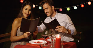 Loving young couple choosing food off a menu Royalty Free Stock Photo