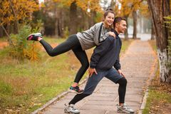 A young couple doing sports in a park in the fall. The girl climbed onto the guy from behind. Outside. A loving young couple are doing sports in a park in the Stock Image