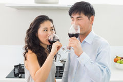 Loving young couple drinking red wine in kitchen Stock Photos