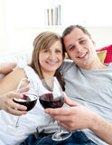 Loving young couple drinking wine on the sofa Royalty Free Stock Photos