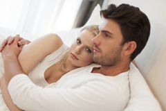 Loving young couple embracing in bed Stock Image