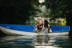 Loving young couple enjoying boat on the lake Royalty Free Stock Image