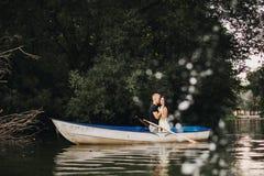 Loving young couple enjoying boat on the lake Royalty Free Stock Photo