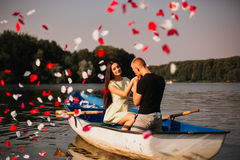 Loving young couple enjoying in the boat, rose Royalty Free Stock Photos