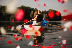 Loving young couple enjoying in the boat, rose Stock Photography