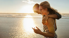 Loving young couple enjoying a day on beach. Side view shot of loving young couple enjoying a day on beach. Beautiful women with her boyfriend walking on the Stock Image
