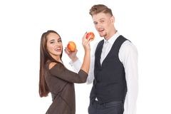 A loving couple, stand and feed each other with ripe and juicy apples. Isolated on white background. Stock Photo