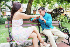 Loving young couple flirting while sitting at a park bench. Stock Image