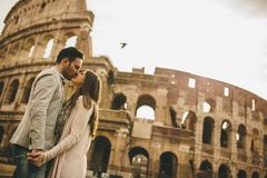 Loving couple in front of the Colosseum in Rome. Loving young couple in front of the Colosseum in Rome, Italy royalty free stock image