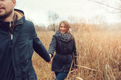 Loving young couple happy together outdoor on cozy warm walk in autumn forest. Seasonal activities Royalty Free Stock Photos