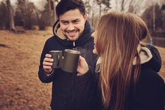 Loving young couple happy together outdoor, drinking tea from thermos, autumn camp Royalty Free Stock Images