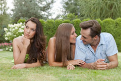 Loving young couple ignoring female friend in park Stock Photos