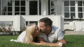 Loving couple kiss lying on the grass near the house. Loving young couple kiss while lying on the grass near the house. slow motion stock video