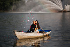 Loving young couple kissing in the boat, rose petals, fountain, blurred Royalty Free Stock Photos