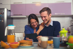 Loving young couple in kitchen by breakfast table in mor Stock Image