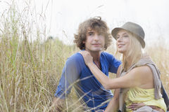 Loving young couple looking away while sitting in field Stock Images