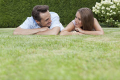 Loving young couple looking at each other while relaxing in park Royalty Free Stock Images