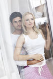 Loving young couple looking through hotel window Stock Images