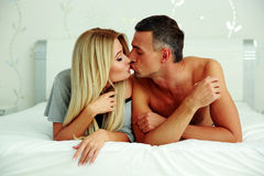 Loving young couple lying on the bed Stock Photos