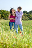 Loving young couple in a poppy field Stock Photography