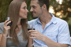 Loving young couple with red wine looking at each other in park Stock Photo