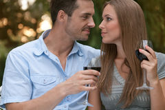 Loving young couple with red wine looking at each other in park Royalty Free Stock Photo