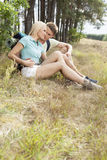 Loving young couple relaxing while hiking in forest Stock Image