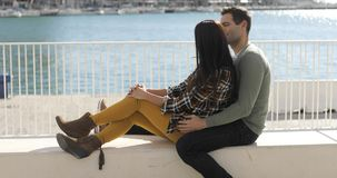 Loving young couple relaxing at the waterfront stock video footage