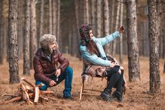 A loving couple is resting in the woods, making selfies on a mobile phone. Royalty Free Stock Image