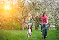 Loving young couple riding bicycles in the spring garden Royalty Free Stock Images