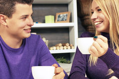 Loving young couple sitting in the cafeteria. Talking and smiling. Drink hot coffee Royalty Free Stock Images