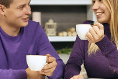 Loving young couple sitting in the cafeteria. Talking and smiling. Drink hot coffee Stock Images