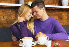 Loving young couple sitting in the cafeteria. Talking and smiling. Drink hot coffee Stock Photo