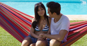 Loving young couple sitting on a hammock Royalty Free Stock Photo