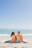 Loving young couple sitting with their surfboards. Loving young couple sitting on the beach with their surfboards Royalty Free Stock Photo