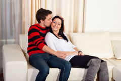 Loving young couple on sofa home Stock Images