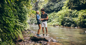 Loving young couple standing by mountain stream. Loving young couple standing together by a mountain stream in forest. Two hikers by stream in woods Stock Photos