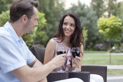 Loving young couple toasting red wine on chairs in park Royalty Free Stock Photography