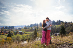 Loving young couple on a walk in colorful autumn landscape in the mountain village. Royalty Free Stock Image