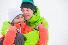 Loving young couple in warm clothing embracing outdoors Stock Photos