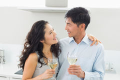 Loving young couple with wine glasses in kitchen Stock Photo